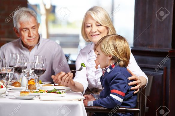 Child eating out with his grandparents in a restaurant
