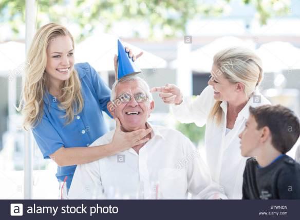 family-celebrating-grandfathers-birthday-at-restaurant-ETWNCN