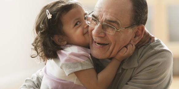 Hispanic girl kissing grandfather